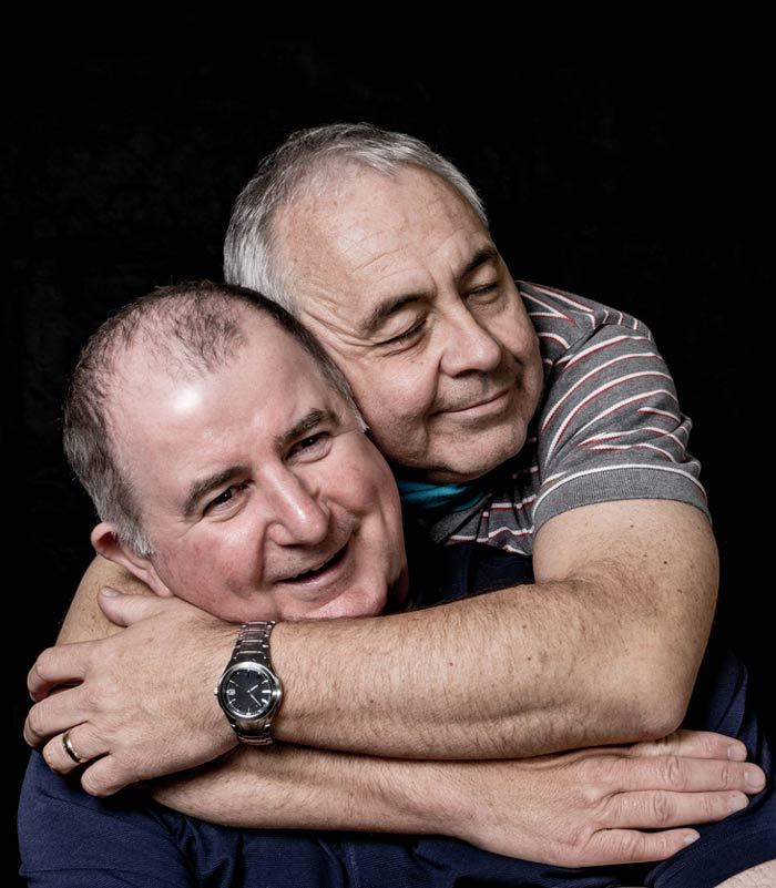 Photo of middle aged gay couple embracing